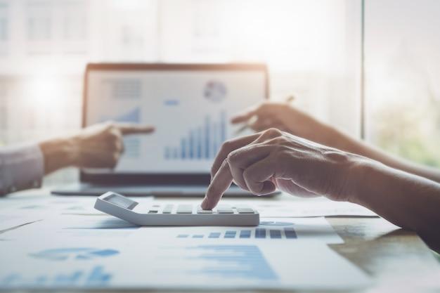 Uomo e associazione di affari facendo uso del calcolatore per rivedere il bilancio annuale con la penna di tenuta e per mezzo del computer portatile al bilancio calcolatore. verifica e verifica dell'integrità prima del concetto di investimento.