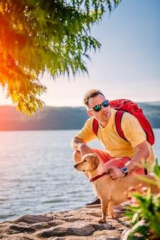 Uomo e cane accovacciati sul bacino di pietra sul mare