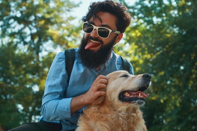 Uomo e cane divertirsi, giocare, fare facce buffe