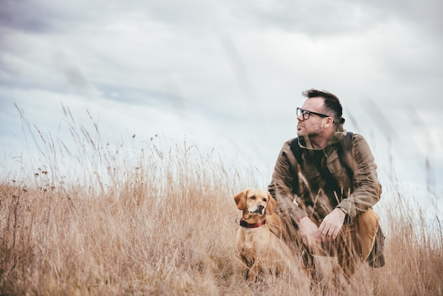Uomo e cane in erba alta