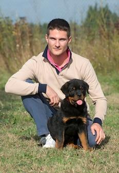 Uomo e cucciolo di rottweiler