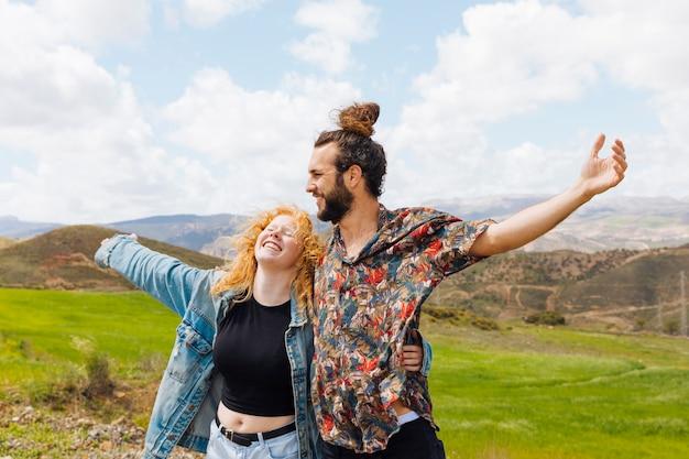Uomo e donna a braccia aperte in natura
