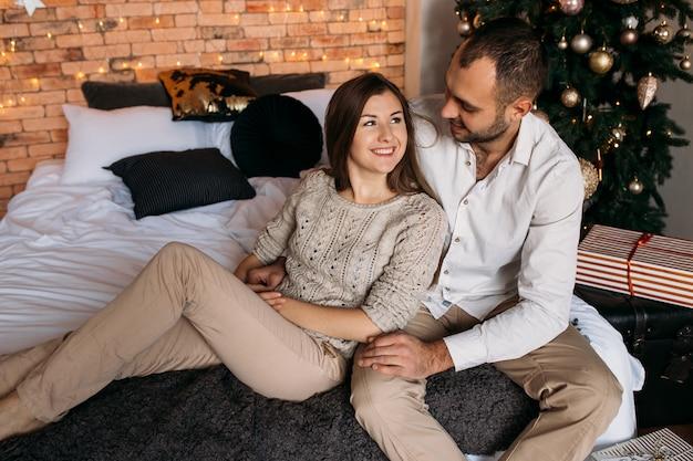 Uomo e donna a casa vicino all'albero di natale. coppia in amore sul letto