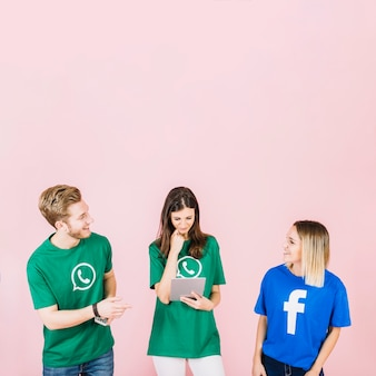 Uomo e donna a guardare l'altro mentre la sua amica utilizzando la tavoletta digitale