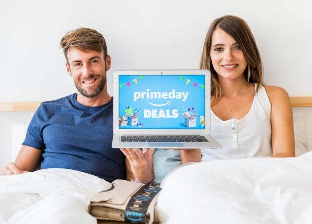 Uomo e donna a letto con il portatile