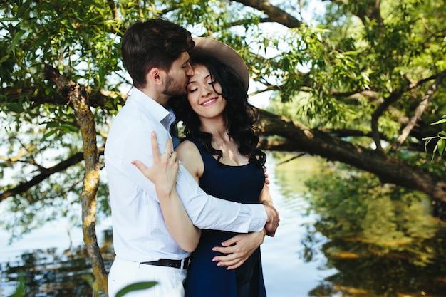 Uomo e donna al lago per trascorrere del tempo l'uno nelle braccia dell'altro