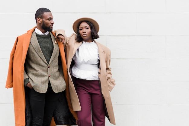 Uomo e donna alla moda che posano con lo spazio della copia