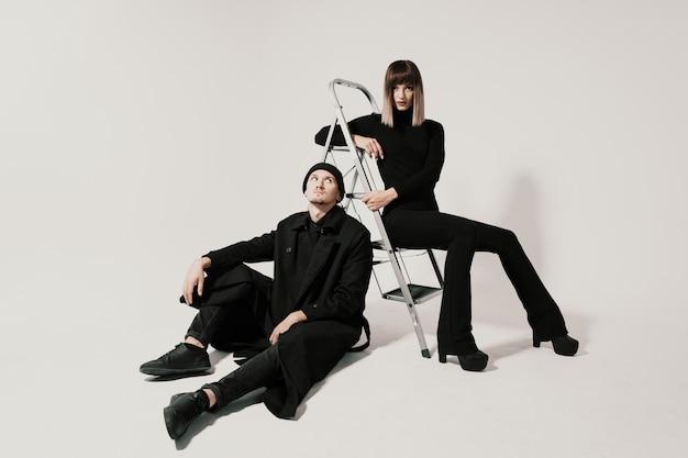 Uomo e donna alla moda che si siedono su una scala