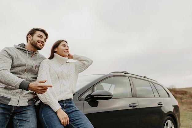 Uomo e donna appoggiata su auto