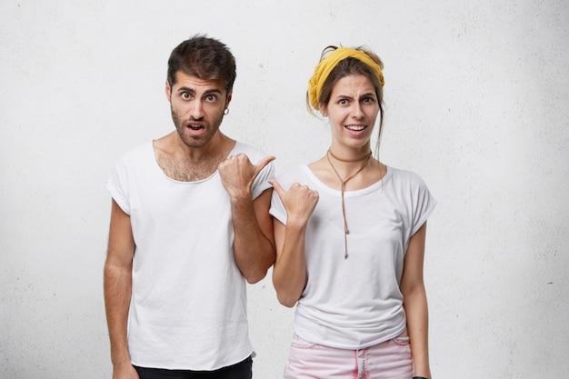 Uomo e donna arrabbiati e infastiditi che affrontano problemi di relazione, indicandosi l'un l'altro, incolpandosi a vicenda. coppia in disaccordo con discussioni, conflitti o litigi. linguaggio del corpo