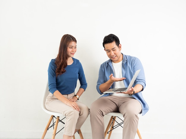 Uomo e donna asiatici che parlano con il computer portatile per l'affare su fondo bianco