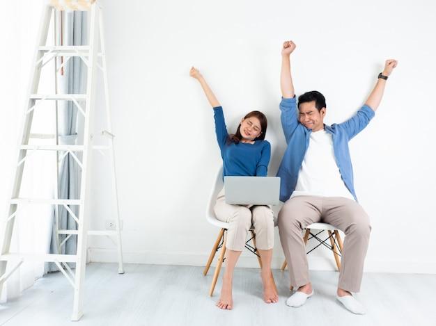 Uomo e donna asiatici che parlano noioso e sonnolento con il computer portatile per l'affare su fondo bianco