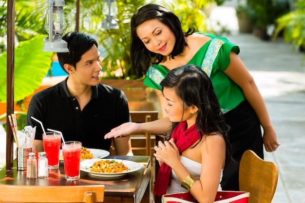 Uomo e donna asiatici in ristorante