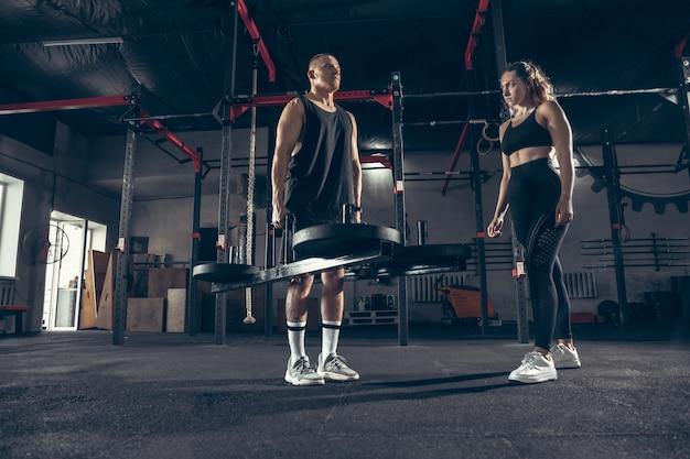Uomo e donna atletici con le teste di legno
