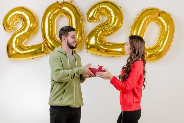 Uomo e donna bei delle coppie con regalo di natale davanti ai palloni del nuovo anno 2020