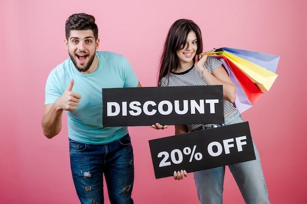 Uomo e donna bei sorridenti felici con lo sconto del 20% sul segno e sui sacchetti della spesa variopinti