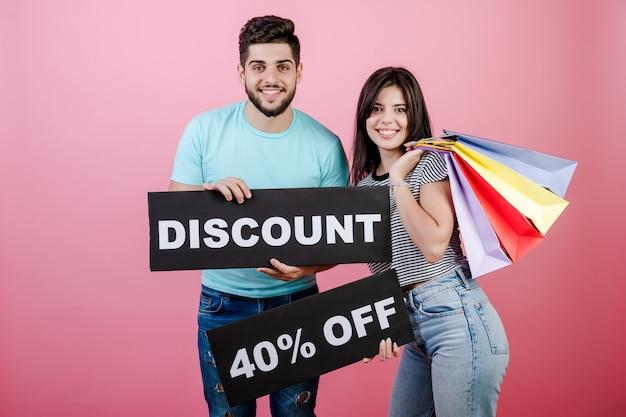 Uomo e donna bei sorridenti felici con lo sconto del 40% sul segno e sui sacchetti della spesa variopinti