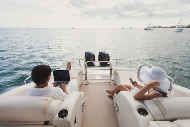 Uomo e donna bei sulla piattaforma dell'yacht con il telefono cellulare e il computer portatile