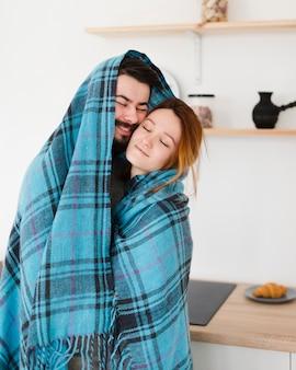 Uomo e donna che abbracciano in una coperta