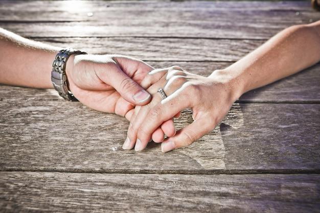 Uomo e donna che accarezzano le mani affettuosamente distese sul legno
