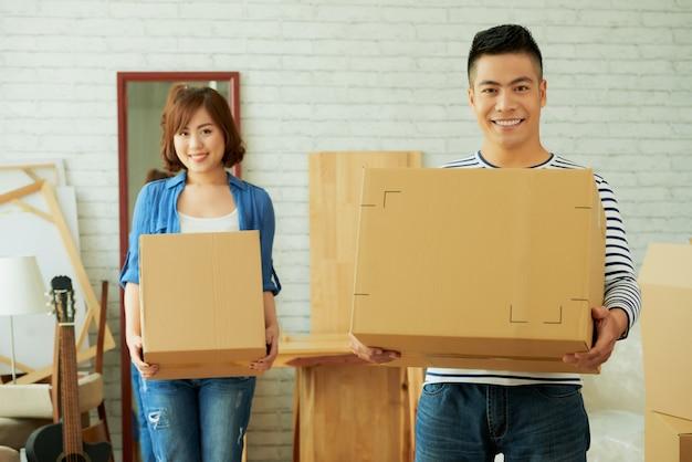 Uomo e donna che affrontano le scatole di cartone della tenuta della macchina fotografica
