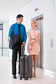 Uomo e donna che arrivano nella hall dell'hotel con la valigia