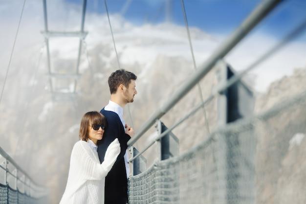 Uomo e donna che attraversano insieme il ponte