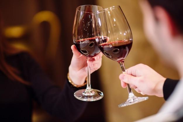 Uomo e donna che bevono vino rosso. nella foto, mani ravvicinate con gli occhiali.