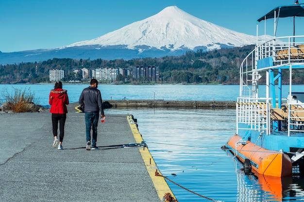 Uomo e donna che camminano lungo un molo