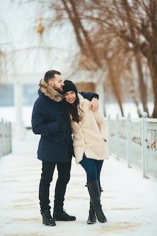 Uomo e donna che camminano nel parco in inverno