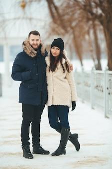 Uomo e donna che camminano nel parco invernale