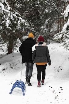 Uomo e donna che camminano nella foresta con la slitta da dietro il colpo
