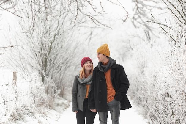 Uomo e donna che camminano nella foresta di inverno
