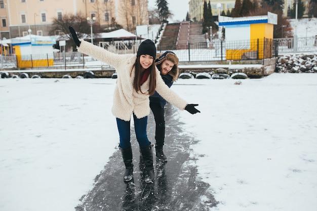 Uomo e donna che cavalcano sul ghiaccio su un lago ghiacciato