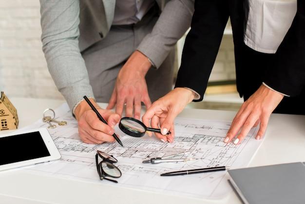 Uomo e donna che controllano un piano di costruzione