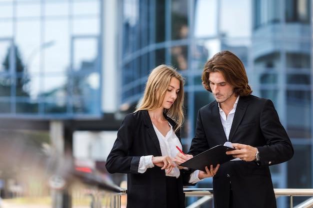 Uomo e donna che controllano una lavagna per appunti