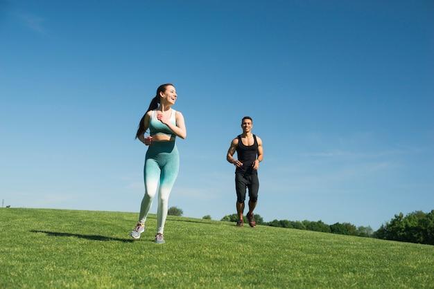 Uomo e donna che corrono all'aperto in un parco