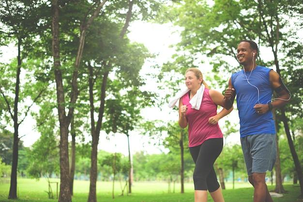 Uomo e donna che corrono nel parco