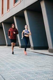 Uomo e donna che corrono nell'ambiente urbano