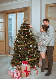 Uomo e donna che decora l'albero di natale
