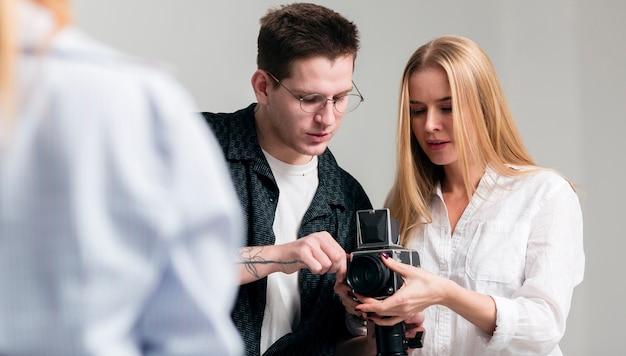 Uomo e donna che esaminano la vista frontale della macchina fotografica