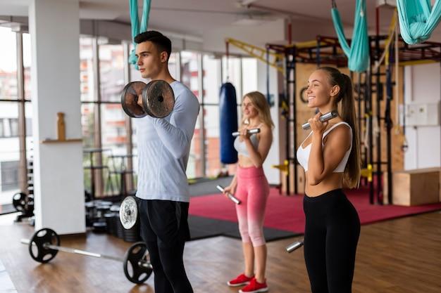 Uomo e donna che fanno allenamento con i pesi