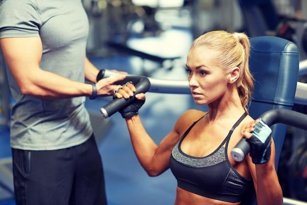 Uomo e donna che flettono i muscoli sulla macchina della palestra