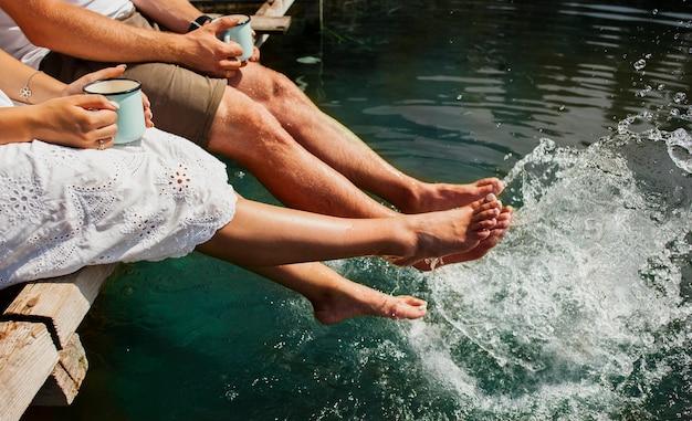 Uomo e donna che giocano in acqua con i piedi