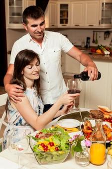 Uomo e donna che godono del vino al tavolo da pranzo