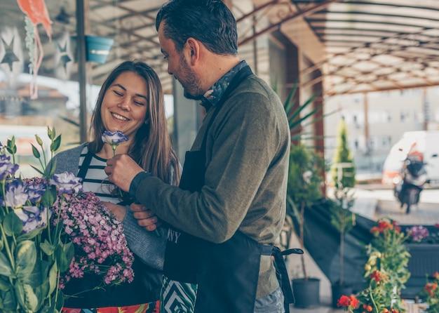 Uomo e donna che guardano i fiori nel negozio di fiori durante il giorno che sembrano felici