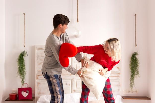 Uomo e donna che hanno una lotta di cuscini in camera da letto