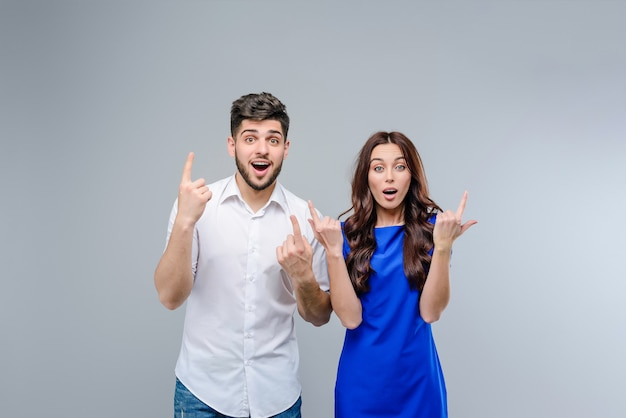 Uomo e donna che indicano in su al copyspace