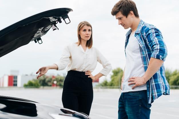 Uomo e donna che lavorano su auto