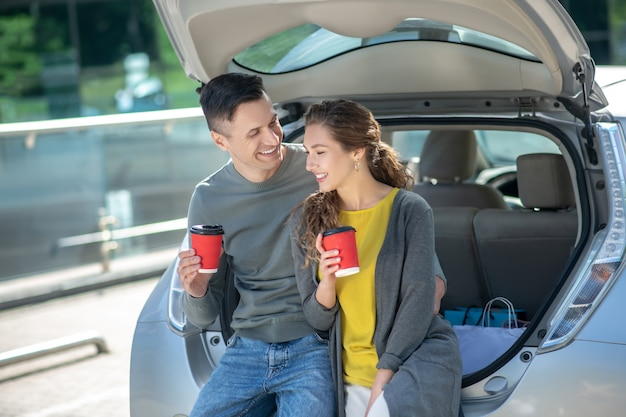 Uomo e donna che mangiano caffè vicino alla sua automobile